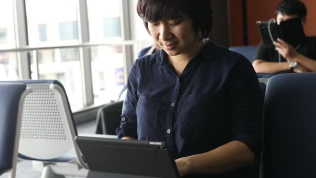 Azië vrouw met behulp van digitale tablet in zonnige luchthaven