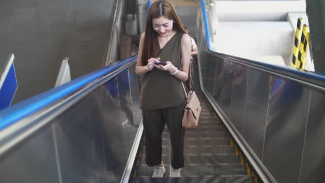 asia frau mit rolltreppe und mit telefon - rucksack stock-videos und b-roll-filmmaterial