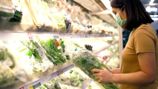 vídeos y material grabado en eventos de stock de asia mujer con máscara facial de compras en supermercado - una mujer de mediana edad solamente
