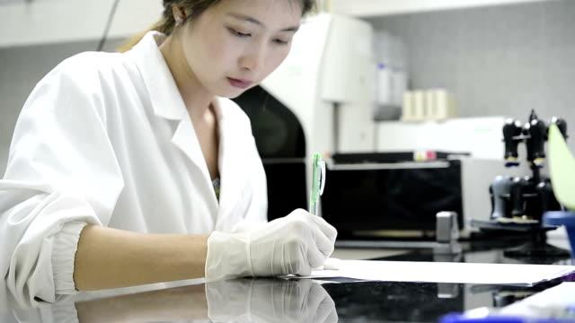 stockvideo's en b-roll-footage met azië vrouwen schrijven van gegevens op papier in laboratorium - elektronische organiser