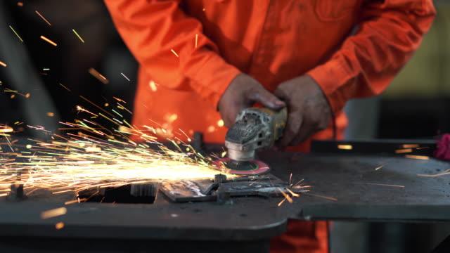 vídeos de stock, filmes e b-roll de trabalhador asiático moendo metal na fábrica - afiado