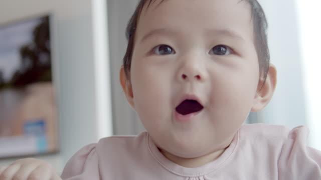 vídeos de stock e filmes b-roll de asian 8 month baby girl enjoy playing on white bed at home. - ensolarado