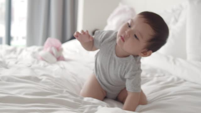 asiatiska 8 månaders baby girl njuta av att spela på vit säng hemma. - krypa bildbanksvideor och videomaterial från bakom kulisserna