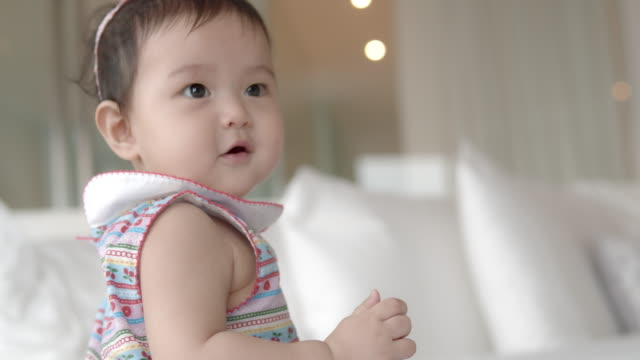 asian 8 month baby girl on red dress enjoy playing on white bed at home. - red dress stock videos & royalty-free footage