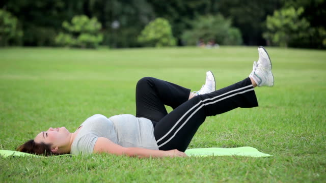 asian a woman lying by exercise leg upwards at the park - overweight child stock videos & royalty-free footage