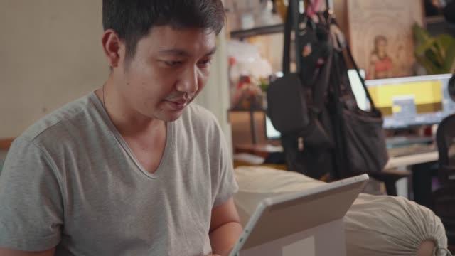 vidéos et rushes de homme adulte asiatique s'asseyent sur la vidéoconférence de lit, travaillant à la maison. - hot desking
