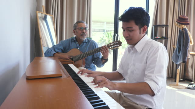 asian adult son enjoy playing piano and senior father playing guitar together in living room at home - son stock videos & royalty-free footage