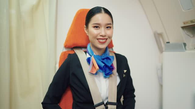 asiatische luftstewardess setzt sicherheitsgurt im flugzeug. - sicherheitsgurt sicherheitsausrüstung stock-videos und b-roll-filmmaterial