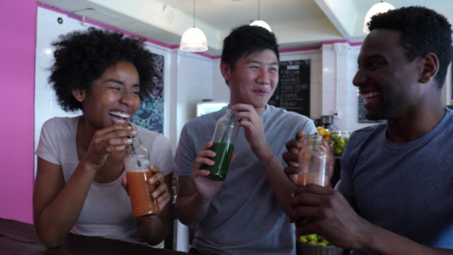 Asian and black friends at a juice bar making a toast with bottled juice laughing and having fun