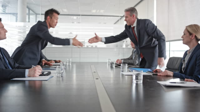 asian and caucasian businessman shaking hands after signing the contract in front of their team members in the conference room - successo video stock e b–roll