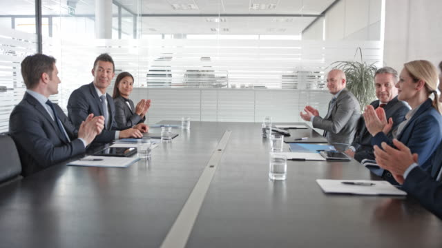 asian and caucasian businessman shaking hands in a meeting in the conference room - accordo d'intesa video stock e b–roll