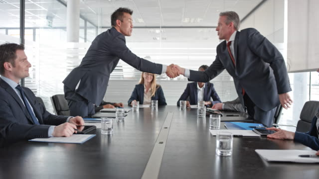 Asian and Caucasian businessman shaking hands in front of their project teams in the conference room