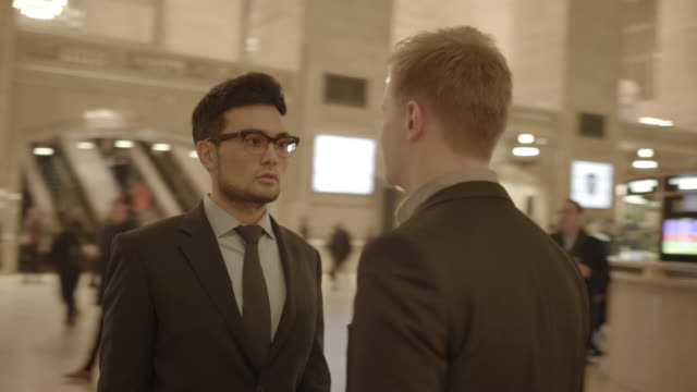 asian and caucasian manager talking about profits. meeting in public space, wearing business wear. - black hair stock videos & royalty-free footage