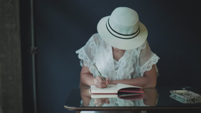 asian artist with white hat and wearing retro white dress is writing and sketching for her leisure activity on weekend while traveling - sketch pad stock videos and b-roll footage