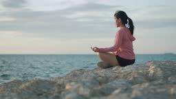 Asian athletic female meditating sitting on stones seaside while sunset.
