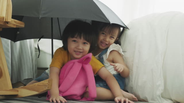 asian baby boy and girl is smiling while hiding under umbrella with peekaboo game - peekaboo game stock videos & royalty-free footage