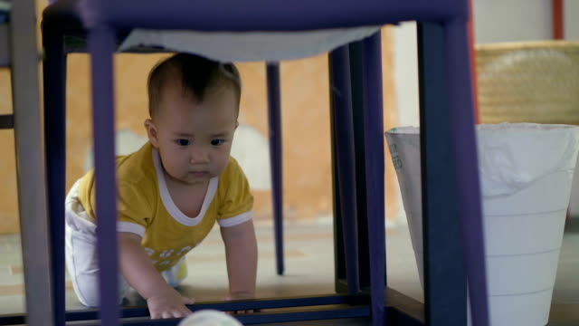 asian baby boy crawling and playing on the floor - soltanto un neonato maschio video stock e b–roll