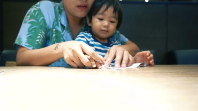 vidéos et rushes de garçon asiatique faisant papier avec maman - origami