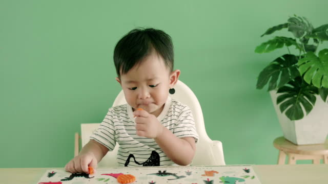 asian baby boy eating a carrot, close up - dirty stock videos & royalty-free footage