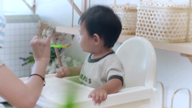 Asian baby boy (6-11months) eating baby food at home
