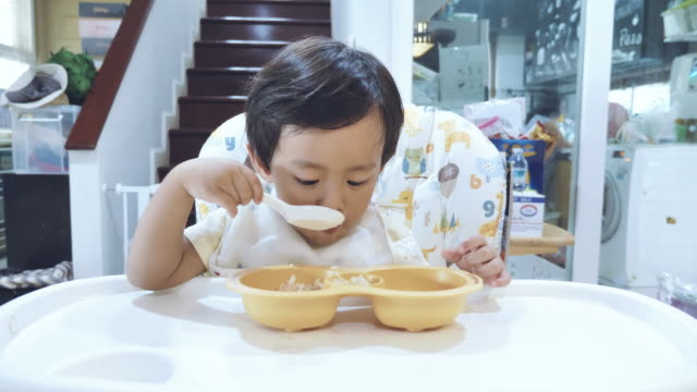 asian baby boy eating carrot in high chair. - 18 23 months stock videos & royalty-free footage