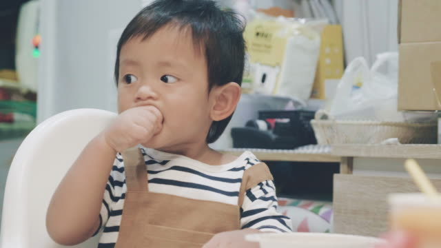 asian baby boy eating carrot in high chair. - 6 11 months stock videos & royalty-free footage