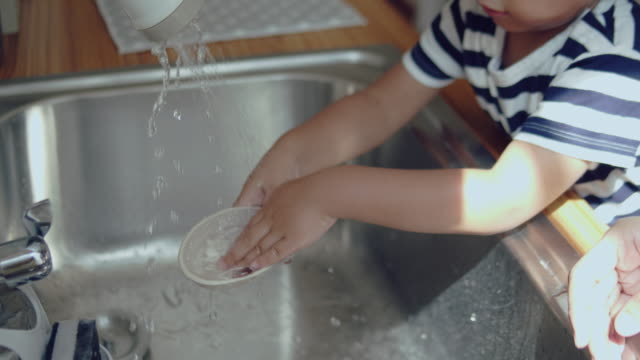 asian baby boy helping mother with the house work - washing up stock videos & royalty-free footage