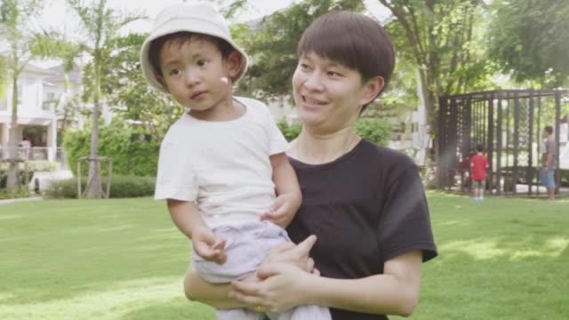 vidéos et rushes de garçon asiatique dans les bras de lesbiennes - trans