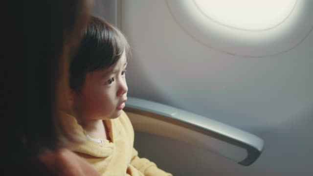 Asian Baby Boy is Fastening Seat belt on Airplane