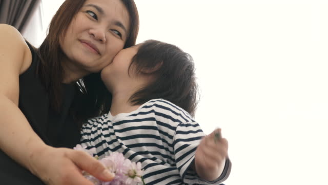 Asian baby boy is kissing his mom and his grandmother-positive emotion