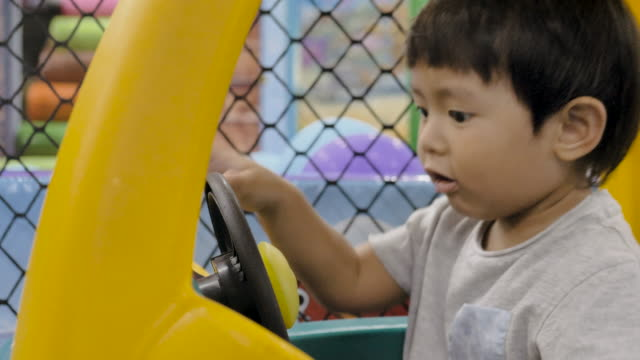 asian baby boy is riding a toy car - learning to drive stock videos & royalty-free footage