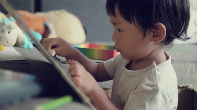 asian baby boy is sketching and drawing on cardboard - 18 23 months stock videos & royalty-free footage
