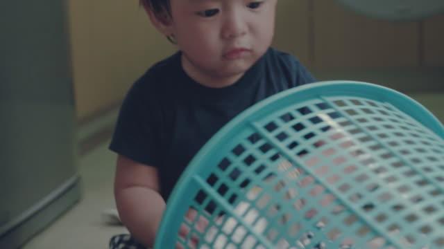 stockvideo's en b-roll-footage met aziatische babyjongen leren te vouwen wasserij thuis - wasmand