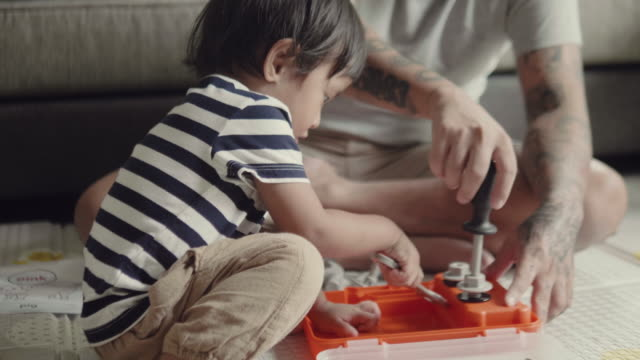 asian baby boy learning to play toy with his father. - toddler stock videos & royalty-free footage