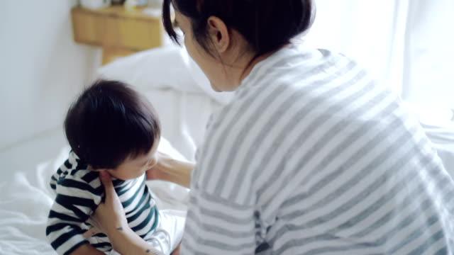 vídeos de stock, filmes e b-roll de bebê asiático (6-11 meses) menino aprendizagem para andar com mãe. - pé humano
