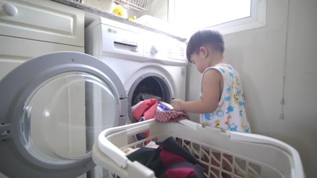 asiatisk pojke laddar kläder för att tvätta kläder i en automatisk tvättstuga hemma - hushållssyssla bildbanksvideor och videomaterial från bakom kulisserna