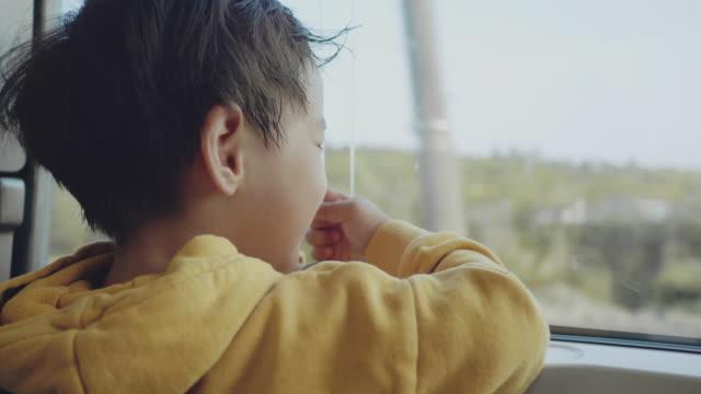 Asiatischer Baby-Junge schaut auf das Fenster. Reisen mit der Bahn
