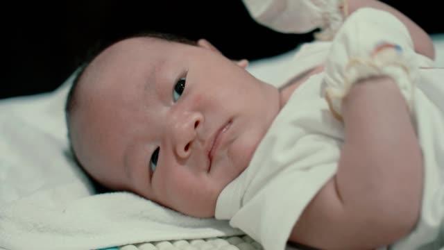 vídeos y material grabado en eventos de stock de niño asiático (0-1 meses) acostado en la cama - 0 1 mes
