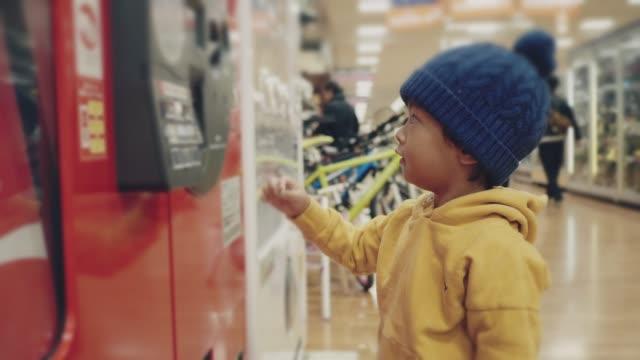 アジアの赤ちゃんの男の子は、自動販売機に水のボトルを拾います。 - machinery点の映像素材/bロール