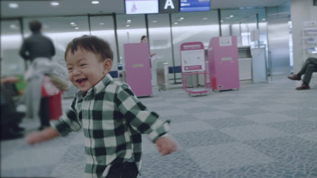 asian baby boy playing in an airport - babies only stock videos & royalty-free footage