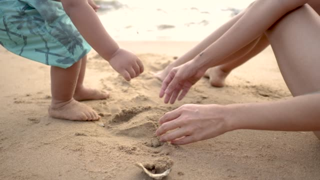 Asian baby boy (12-23 months) playing in sand with mother at Pattaya beach. Chonburi, Thailand.