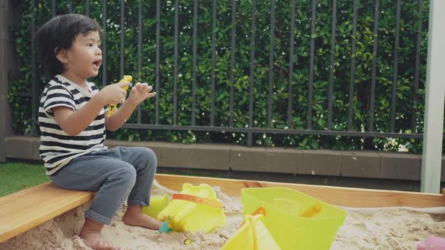 vídeos y material grabado en eventos de stock de asiático bebé niño jugando fuera en caja de arena en el patio trasero - 2 kid in a sandbox