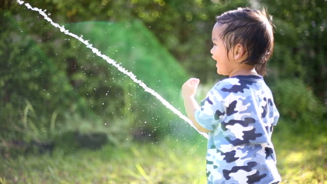 asian baby boy playing rubber tube in garden. - ethnicity stock videos & royalty-free footage