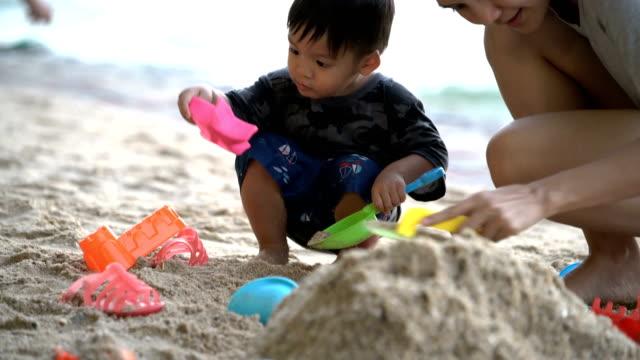 asiatisches baby boy spielen sand mit mutter am strand. - 35 39 years stock-videos und b-roll-filmmaterial