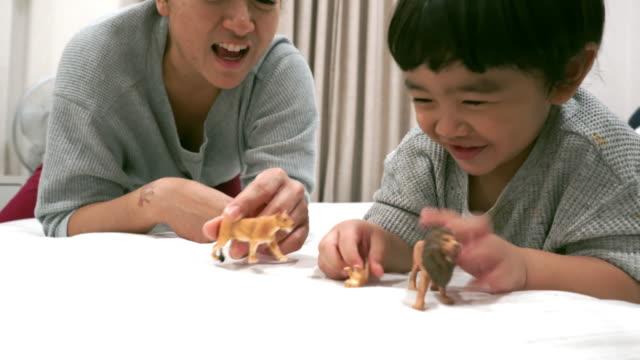 vídeos de stock, filmes e b-roll de bebé asiático que joga o animal do brinquedo - animal de brinquedo