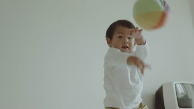 Asiatisches Baby Boy mit Ball spielen.