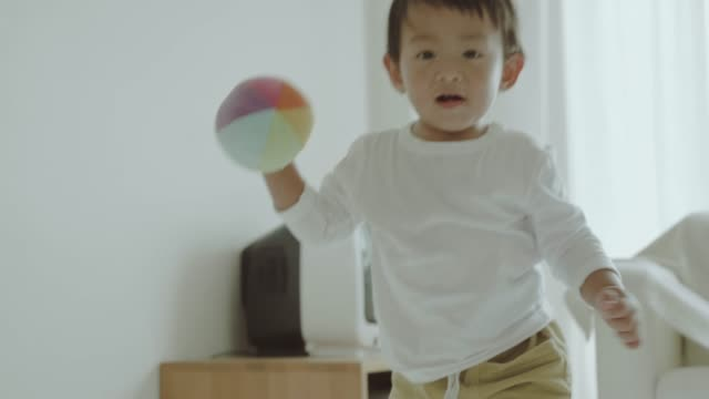 Asian baby boy playing with ball.