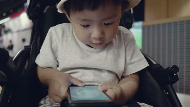 Asian baby boy playing with smartphone.