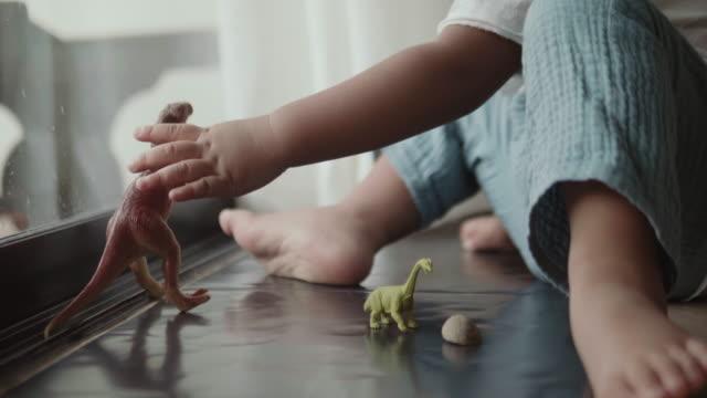 vídeos de stock e filmes b-roll de asian baby boy playing with toy dinosaurs in room - arranjo