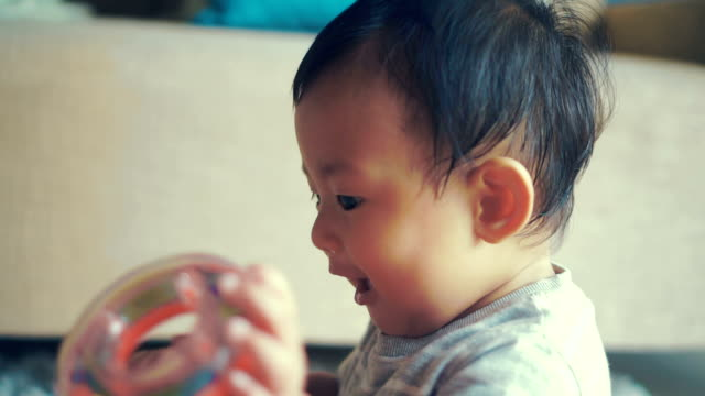 Asian baby boy playing with toys.